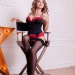 Istanbul escorts woman Lada is sitting in the wooden chair in a candid pose exposing her breasts covered with a lingerie matter of black-and-red color to your affection