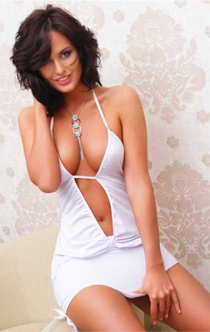 One of escort agency girls is fabulous in this white dress with open breasts holding her arm on the bottom of an attire to close the view from below