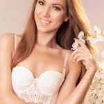VIP escort Istanbul girl is holding a flower in a hand and wears a white tight-fitting bra